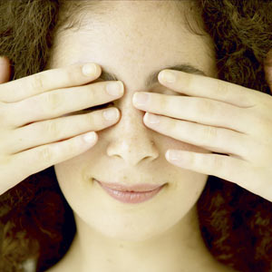 Прикрывает глаза ладонями