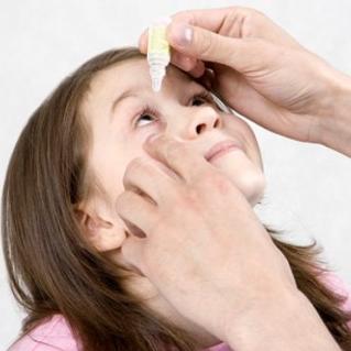 Капает глаза ребенку