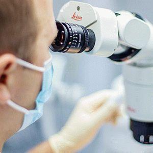 Врач смотрит в микроскопом