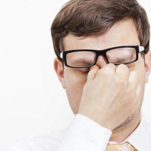 Мужчина в очках трет глаза
